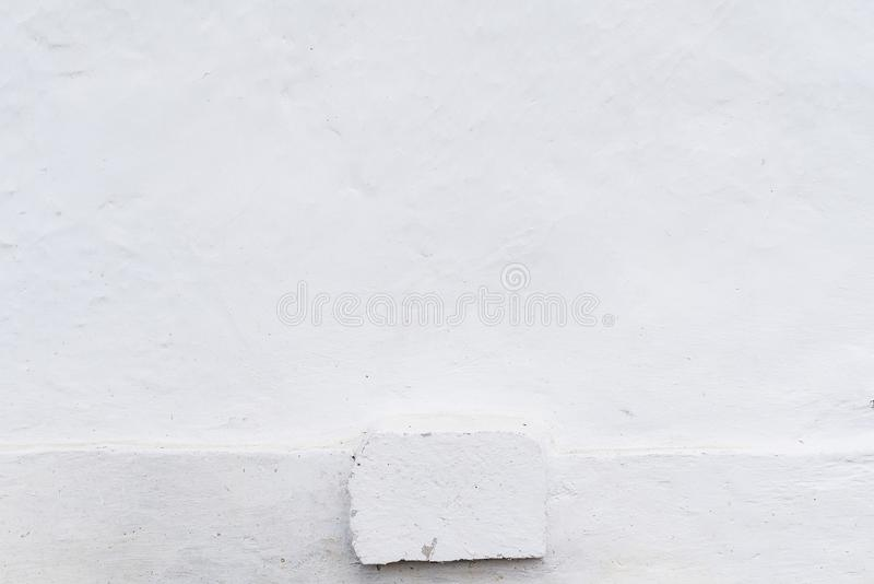 Adobe blanqueó la pared en color blanco natural, base sucia, de madera, rastros de cepillo, fondo con el espacio de la copia para imágenes de archivo libres de regalías