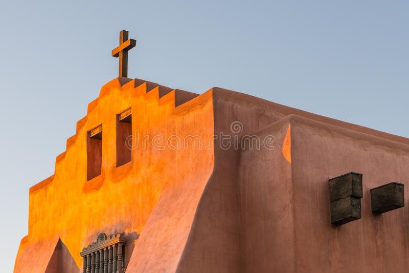 Adobe church and rustic wooden cross glow in golden evening light in Santa Fe, New Mexico. Old adobe mission style church and rustic wooden cross glowing in the stock image
