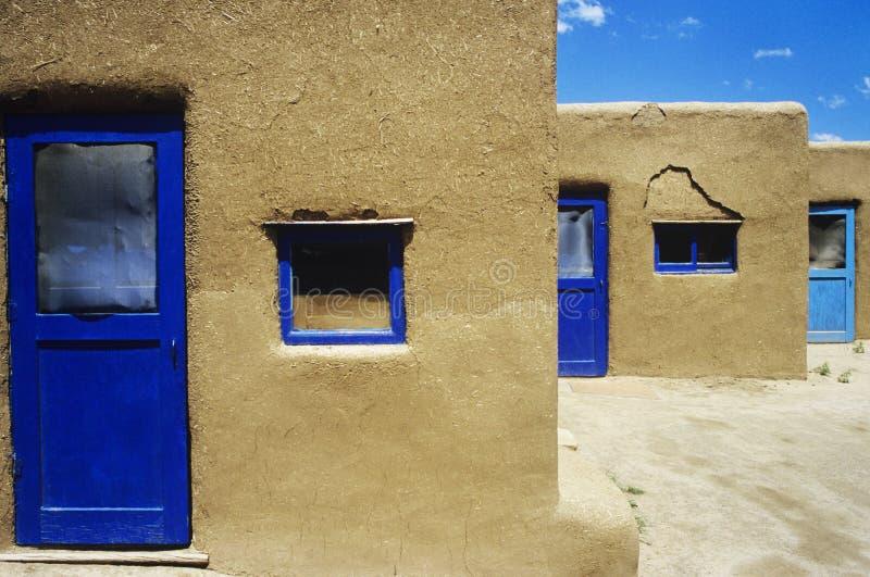 Adobe-Häuser mit blauen Fenstern und Türrahmen lizenzfreie stockbilder