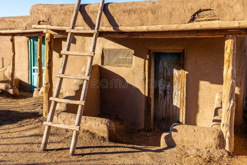Adobe house in the Native American Taos Pueblo. TAOS PUEBLO, NEW MEXICO / UNITED STATES - NOVEMBER 19, 2015: A still-inhabited  traditional adobe house in the stock photo