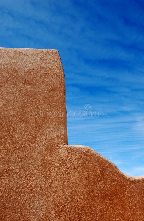 Adobe Wall. Architectural detail of an adobe wall against a brilliant blue sky royalty free stock photos