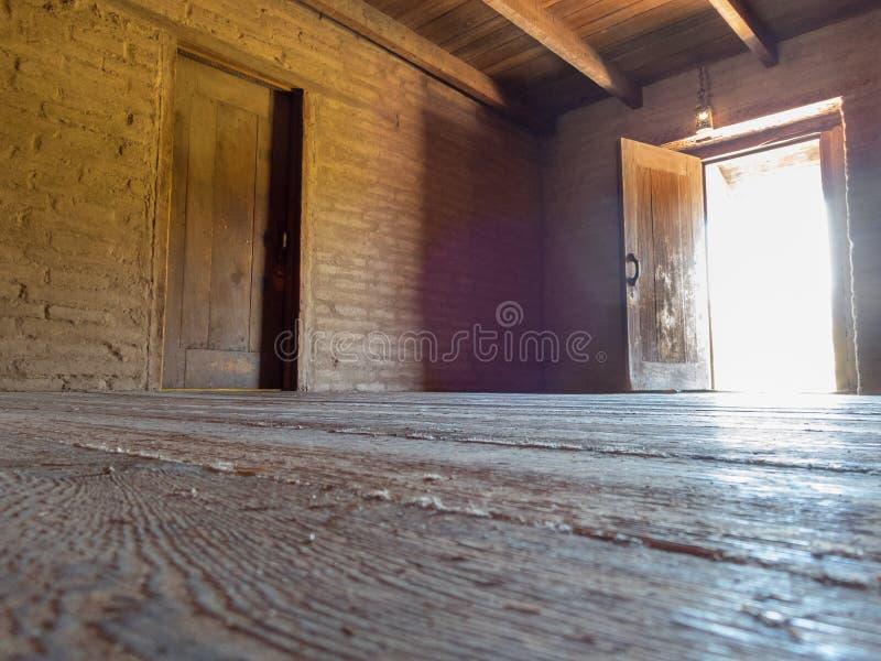 Adobe walls, wood floor and open door. Open exterior door, adobe walls and wooden floor, historic fort building stock photo