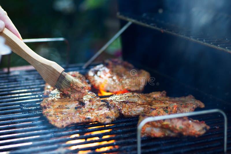 Adobo de la carne durante el asado a la parilla foto de archivo