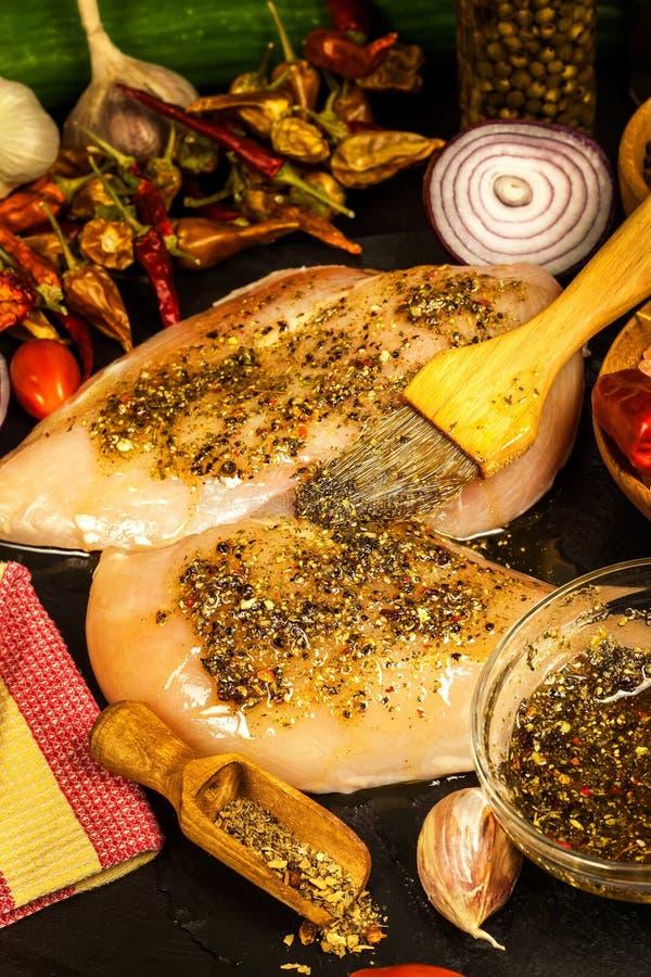 Adobo de la pimienta y pimienta de chiles para el filete del pollo Dieta de la prote?na Pechuga de pollo cruda en parrilla fotografía de archivo
