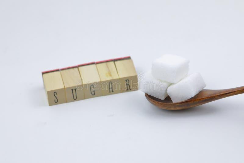 Adoce cubos três cubos do açúcar em um caráter de letra de madeira do açúcar da colher no fundo branco imagem de stock