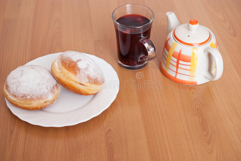 Adoce filhóses revestidas, um vidro do chá do fruto e o potenciômetro do chá na placa branca no fundo de madeira marrom imagens de stock royalty free