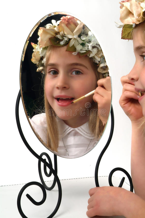Adolable little girl looking in a mirror stock photography