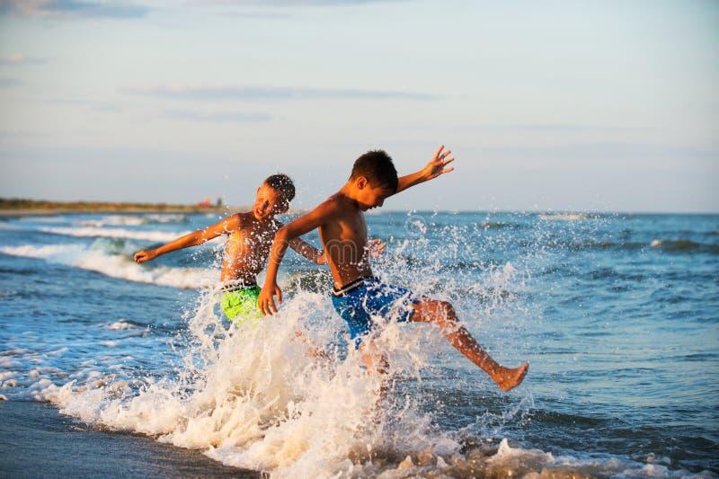 Adolescência de dois meninos que joga na água do mar que espirra o wat dos pés fotografia de stock