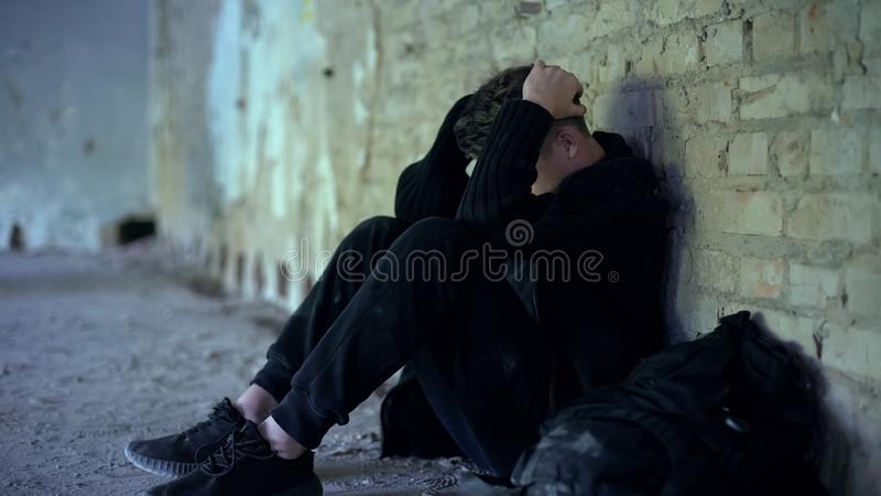 Adolescence problems, teen boy hiding in abandoned building, escape from bully royalty free stock image