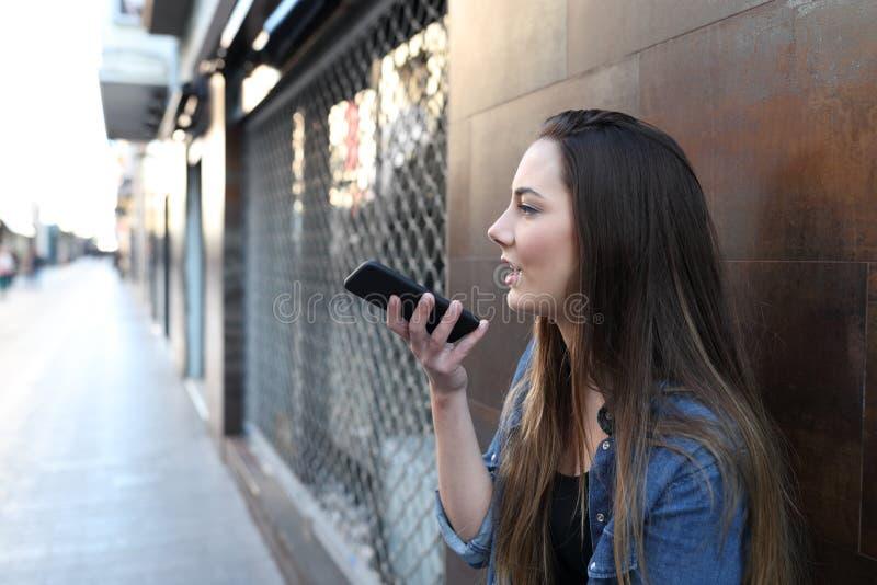 Adolescencia usando el reconocimiento vocal en el teléfono elegante en la calle fotos de archivo