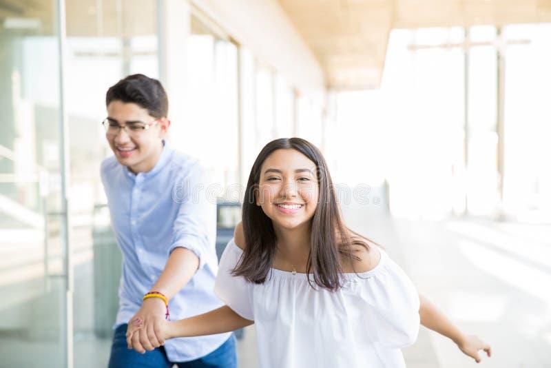 Adolescencias alegres que corren en pasillo en la alameda de compras imágenes de archivo libres de regalías