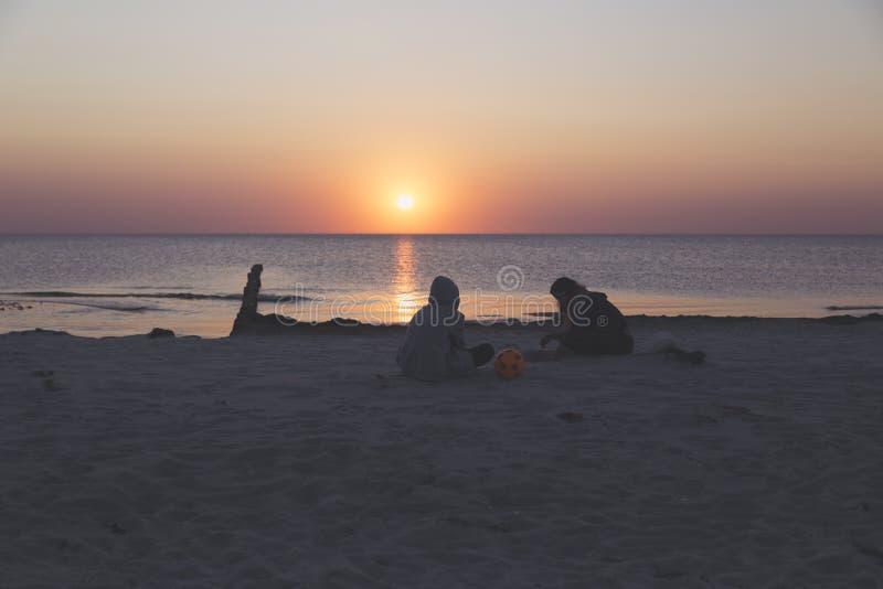 Adolescencias de la remolque que se sientan en la playa fotos de archivo