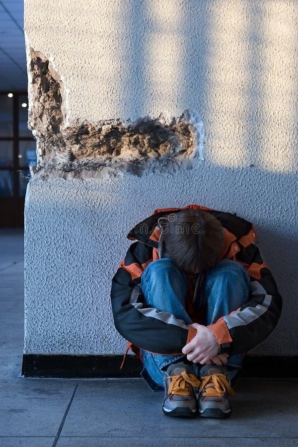 Adolescencias del muchacho que se sientan en el suelo solamente en ciudad imagenes de archivo