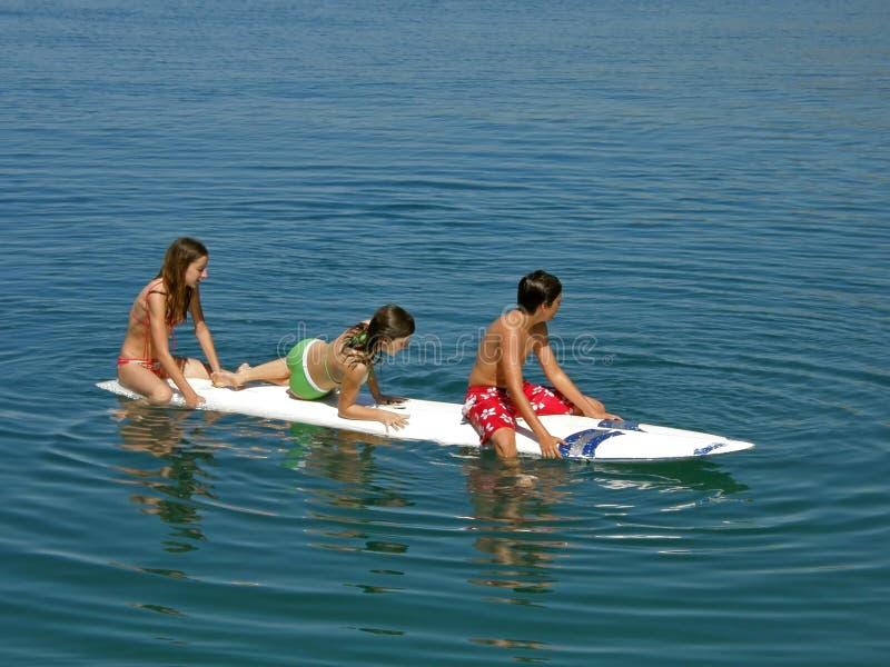Adolescencias en el escritorio que practica surf imagen de archivo