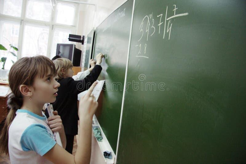 Adolescencias en la lección de la matemáticas en la escuela fotos de archivo libres de regalías