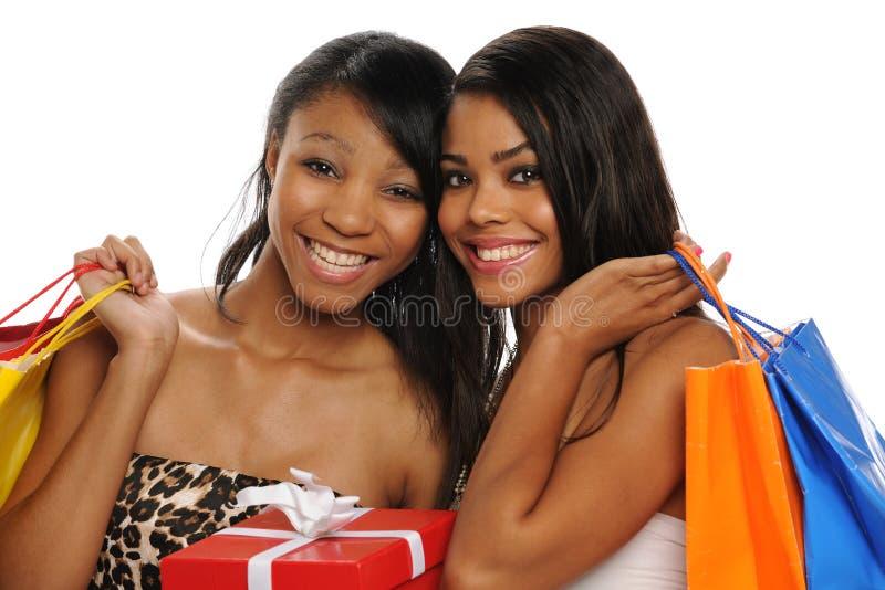 Adolescencias hermosas que sostienen bolsos de compras foto de archivo