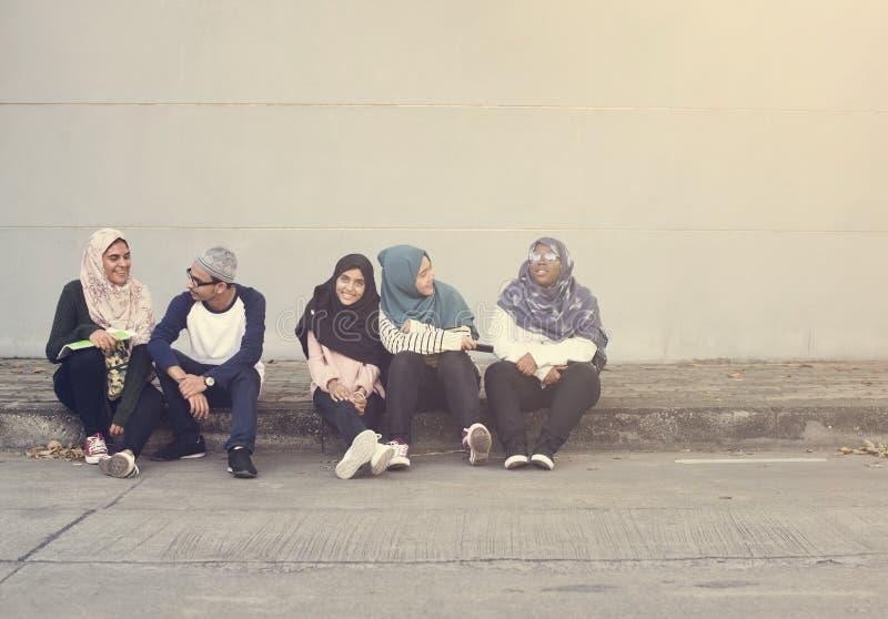 Adolescencias musulmanes que hablan junto en la acera fotografía de archivo