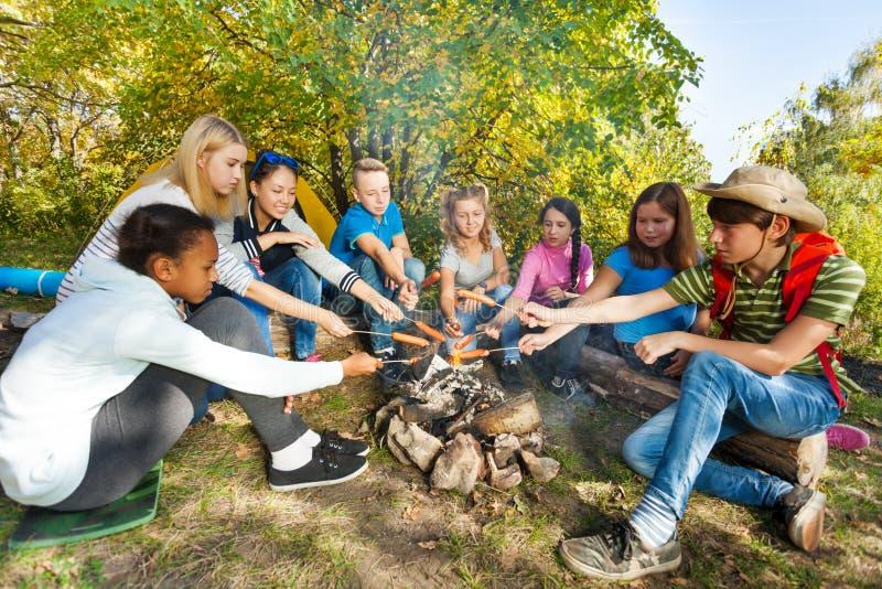 Adolescencias que asan a la parrilla las salchichas en cierre de la sentada del sitio para acampar fotos de archivo