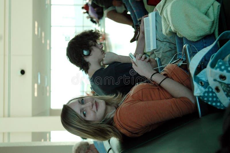 Adolescencias que esperan del aeropuerto imagen de archivo libre de regalías