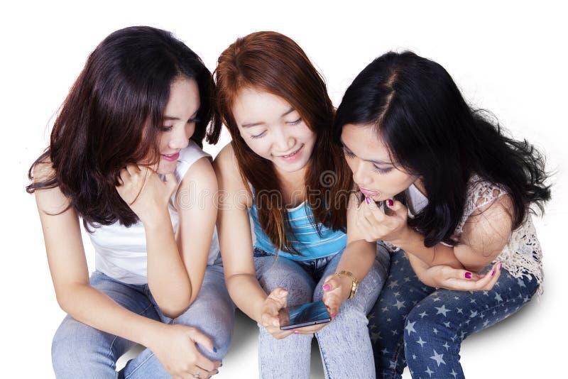 Adolescencias que leen el mensaje junto en el teléfono móvil fotografía de archivo