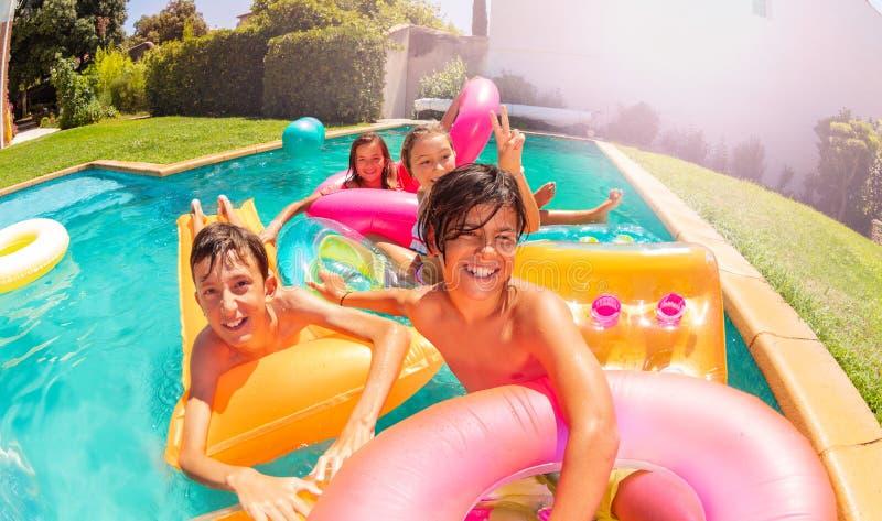 Adolescencias que se divierten en la fiesta en la piscina de la natación del aire abierto fotos de archivo libres de regalías