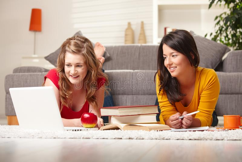 Adolescencias sonrientes que aprenden en suelo imagen de archivo libre de regalías