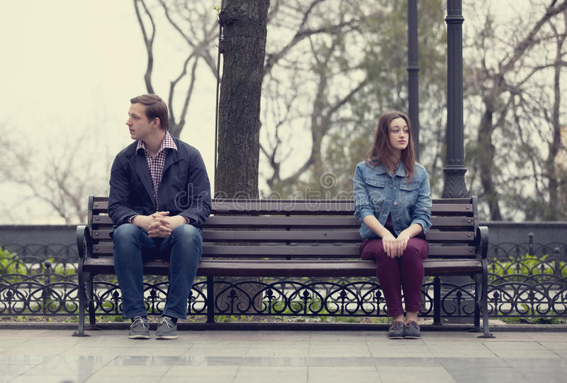 Adolescencias tristes que se sientan en el banco en el parque imagen de archivo libre de regalías