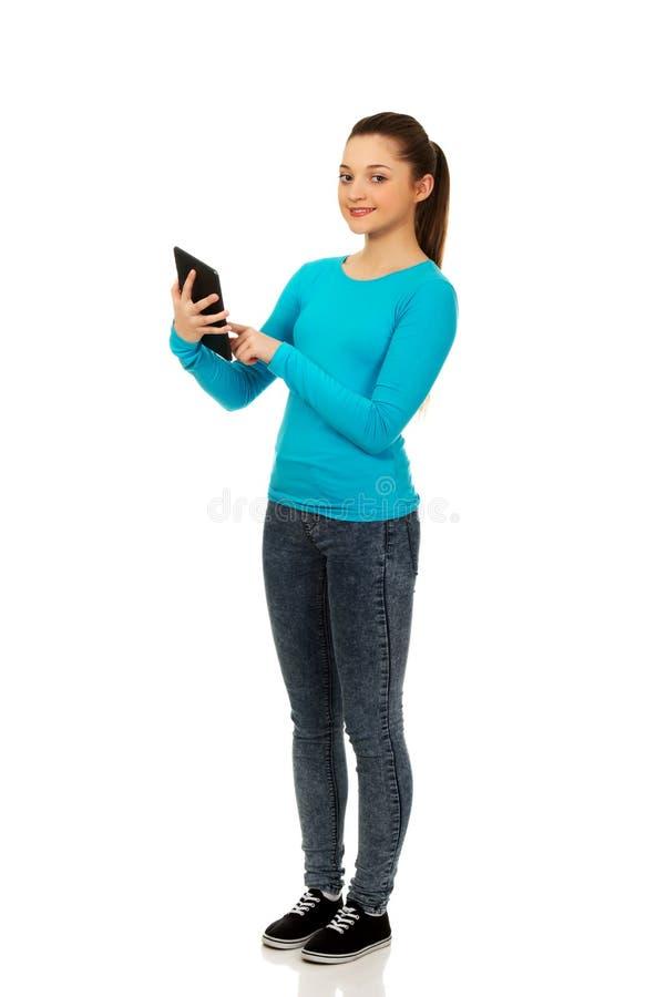 Adolescent à l'aide d'un comprimé images stock
