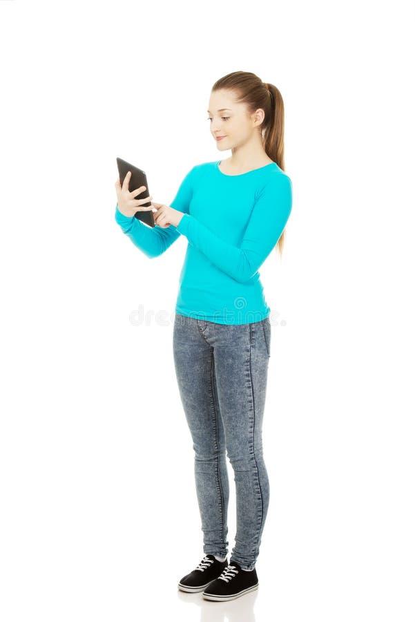 Adolescent à l'aide d'un comprimé image stock