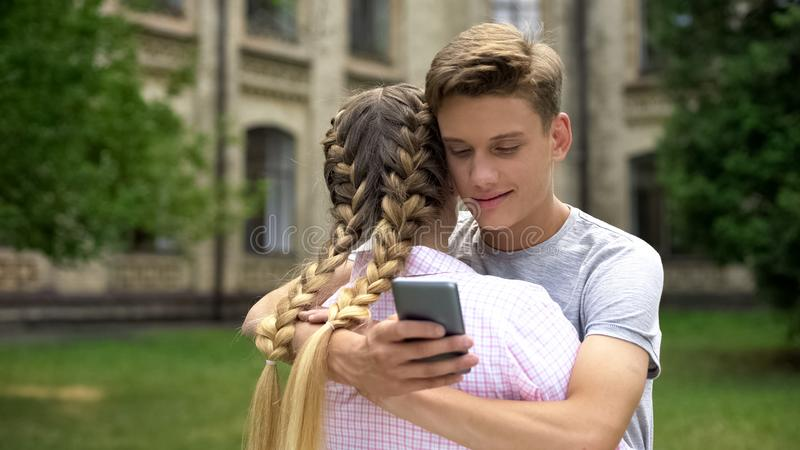 Adolescent à l'aide du téléphone portable tout en étreignant l'amie, absorbée par les réseaux sociaux photos stock