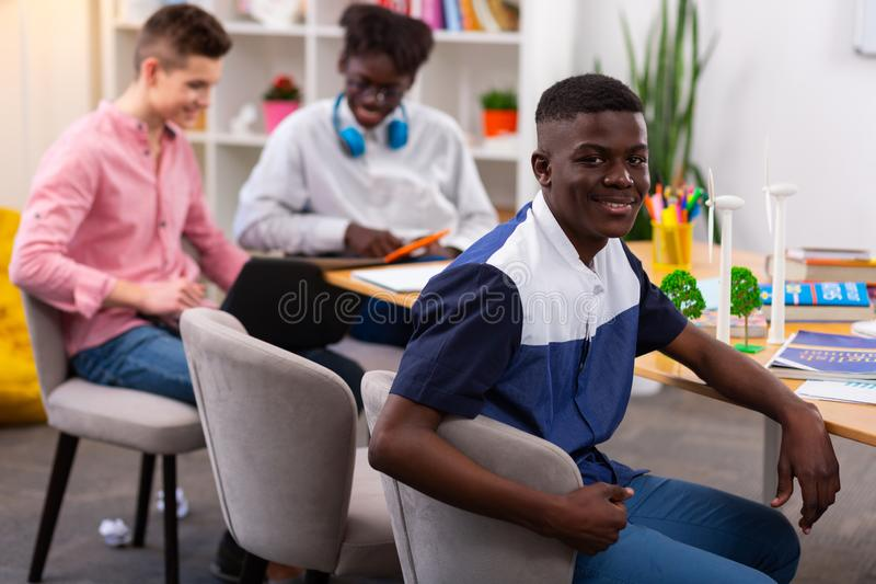 Adolescent à la peau foncée utilisant le T-shirt intéressant se reposant à la table image stock