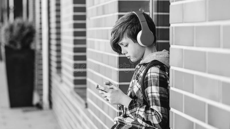 Adolescent écoutant la musique dehors Garçon élégant à l'aide du téléphone dans l'environnement urbain Adolescent heureux utilisa images stock
