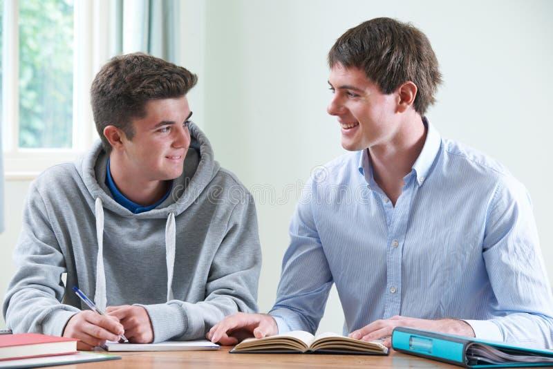 Adolescent étudiant avec le tuteur à la maison image stock