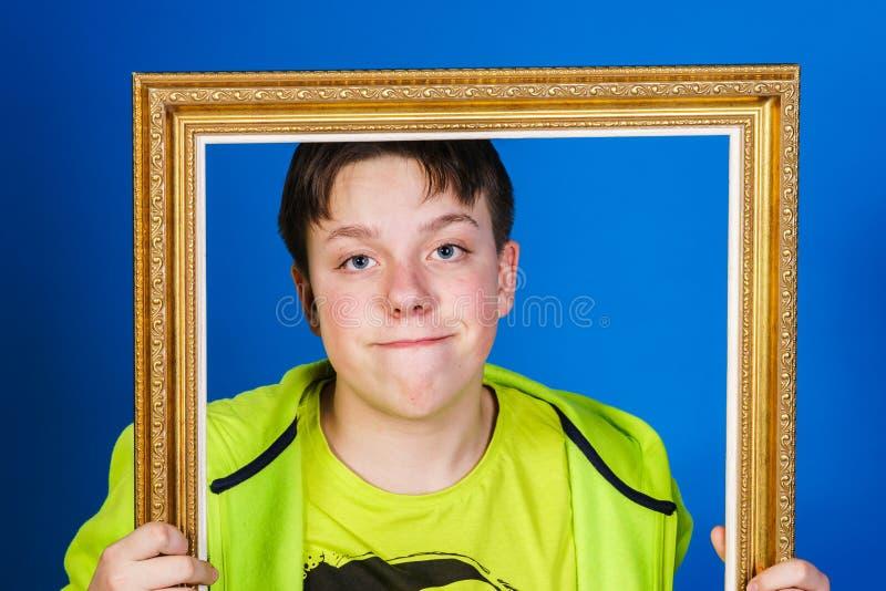 Adolescent affectif posant avec le cadre de tableau images stock