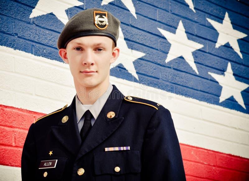 Adolescent américain dans le mur de Front Of United States Flag image stock