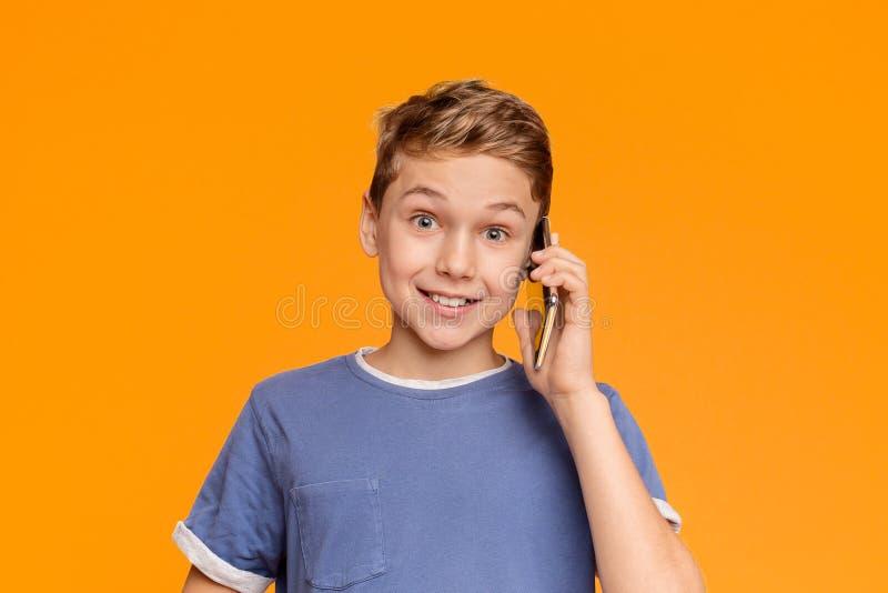Adolescent amical parlant sur le téléphone portable, souriant à la caméra photographie stock