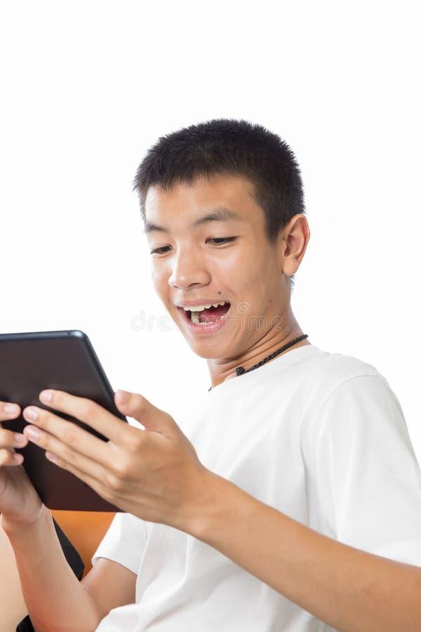 Adolescent asiatique à l'aide de son comprimé avec sentiment heureux photos libres de droits