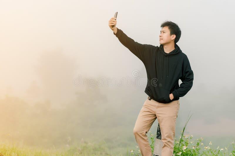 Adolescent asiatique de gar?on portant le support noir d'habillement d'hiver pour prendre des photos de vous-m?me avec un t?l?pho image stock