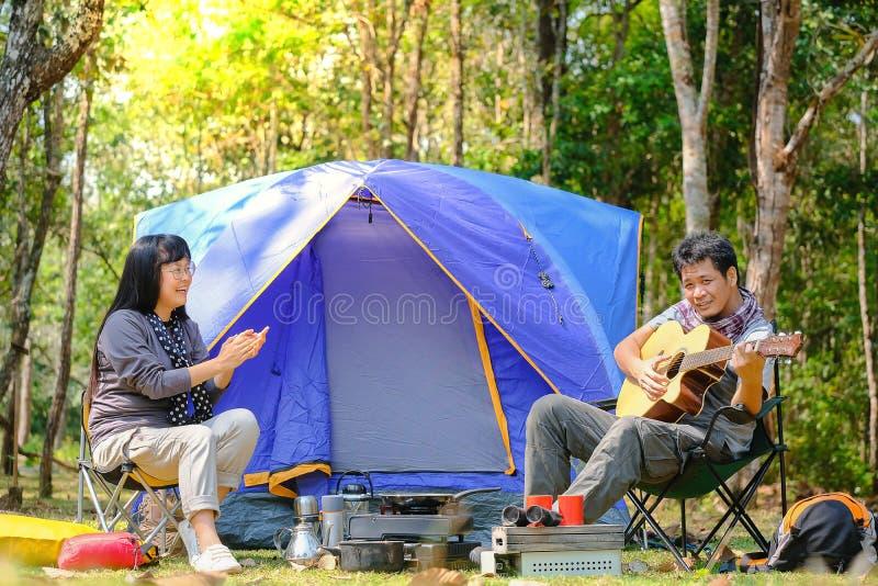 Adolescent asiatique jouant l'avant de guitare de la tente de camping bleue de toile sur le visage heureux de sourire de champ d' image stock