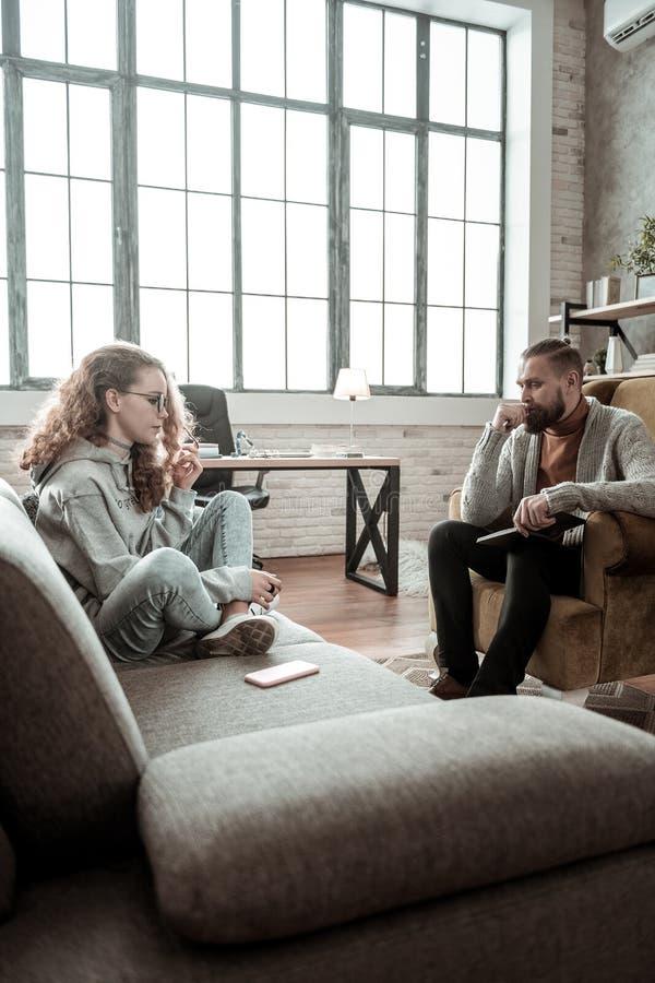 Adolescent aux cheveux foncés bouclé croisant ses jambes se reposant sur le sofa photos libres de droits