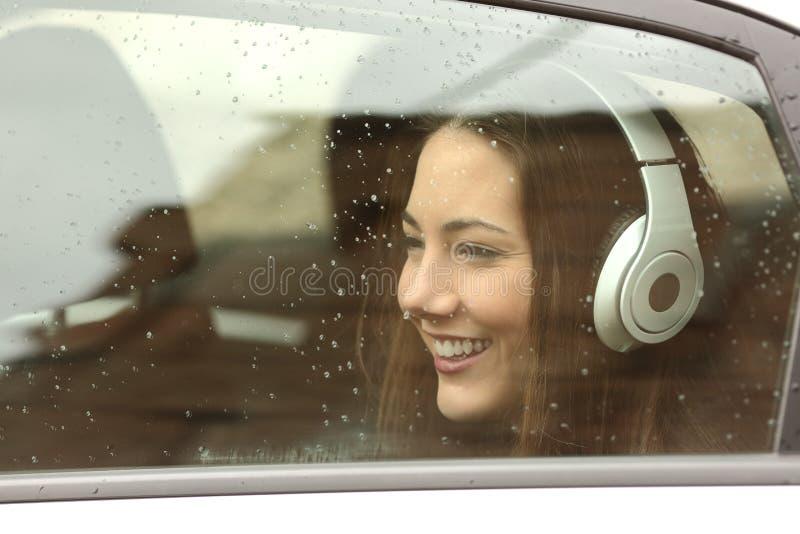 Adolescent avec des écouteurs écoutant la musique dans une voiture photos libres de droits