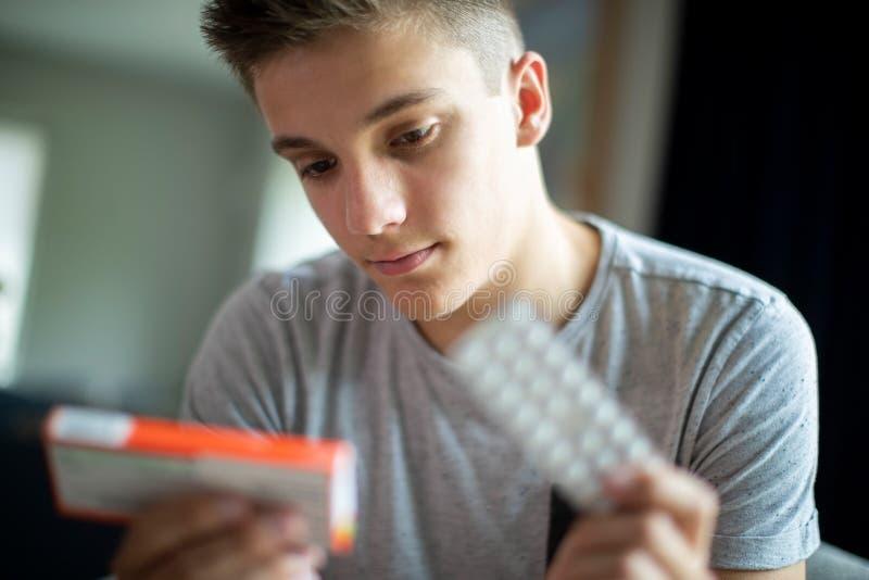 Adolescent avec des problèmes de santé mentale prenant le médicament à la maison image libre de droits