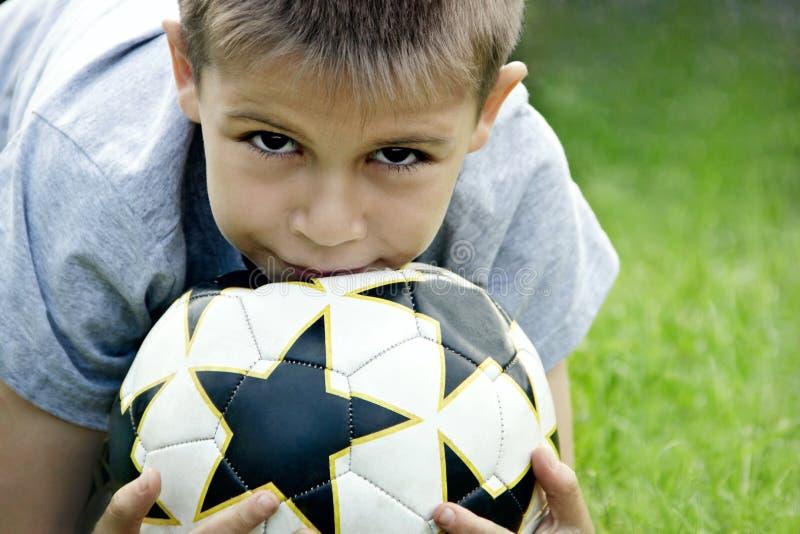 Adolescent avec du ballon de football dans des ses mains dans la perspective du stade image libre de droits