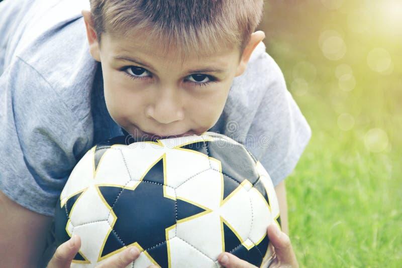 Adolescent avec du ballon de football dans des ses mains dans la perspective du stade tonalité photographie stock libre de droits