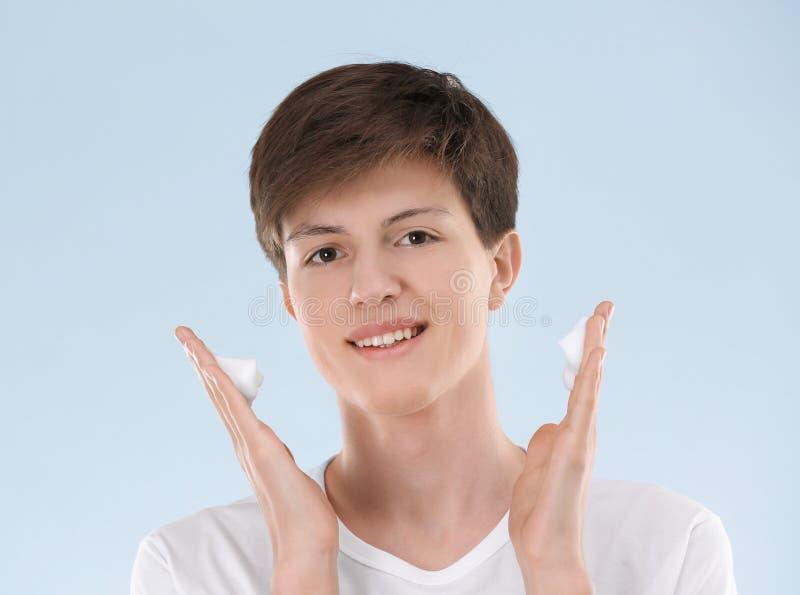 Adolescent avec la peau de problème appliquant l'anti crème d'acné image stock