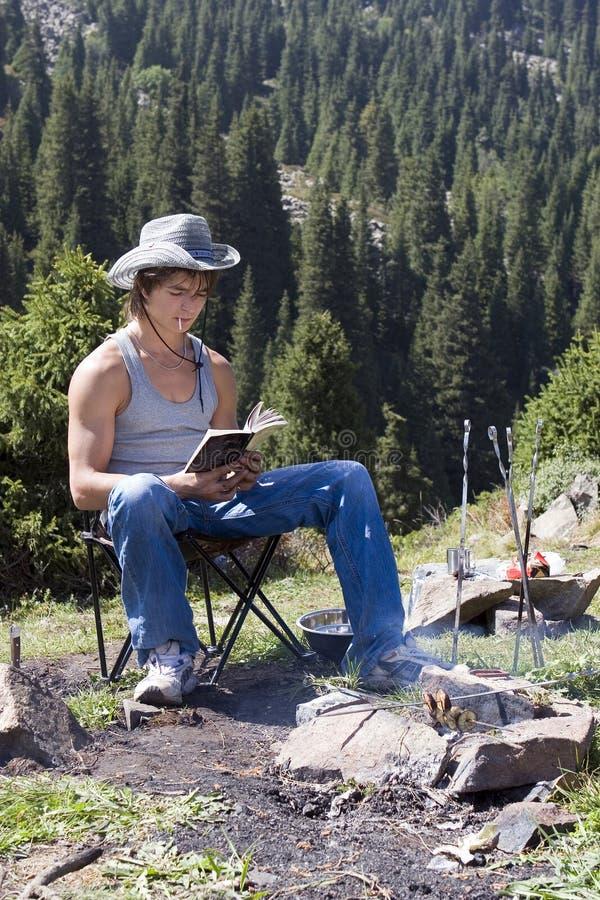 Adolescent avec le livre dans la hausse de montagne image stock