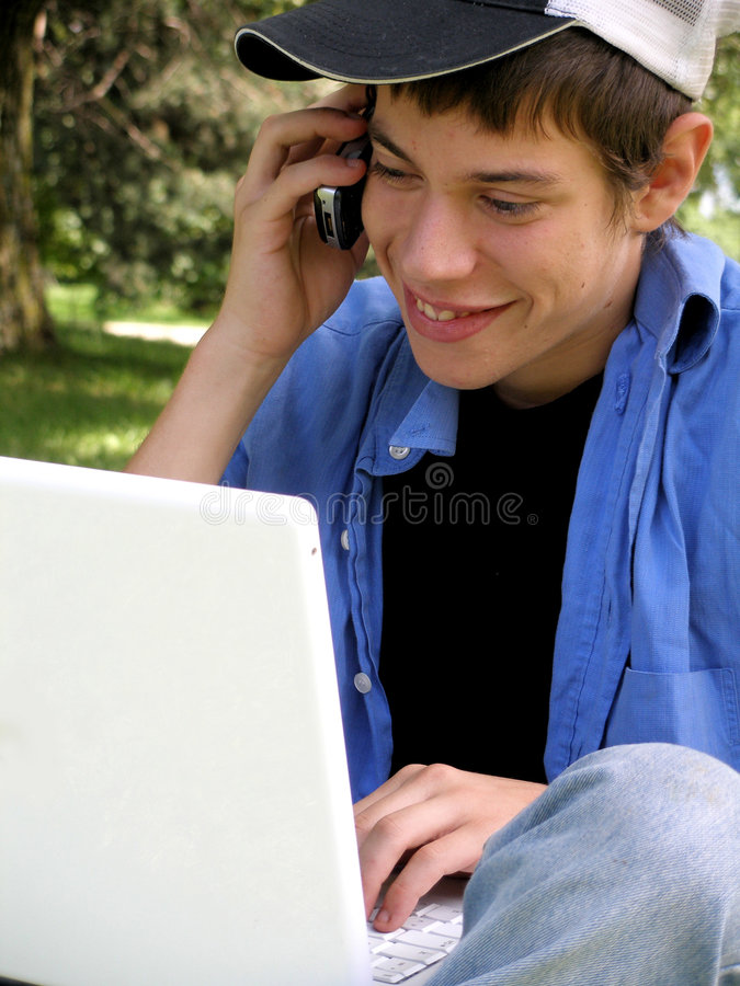 Adolescent avec un ordinateur portatif et cellulaire photo libre de droits