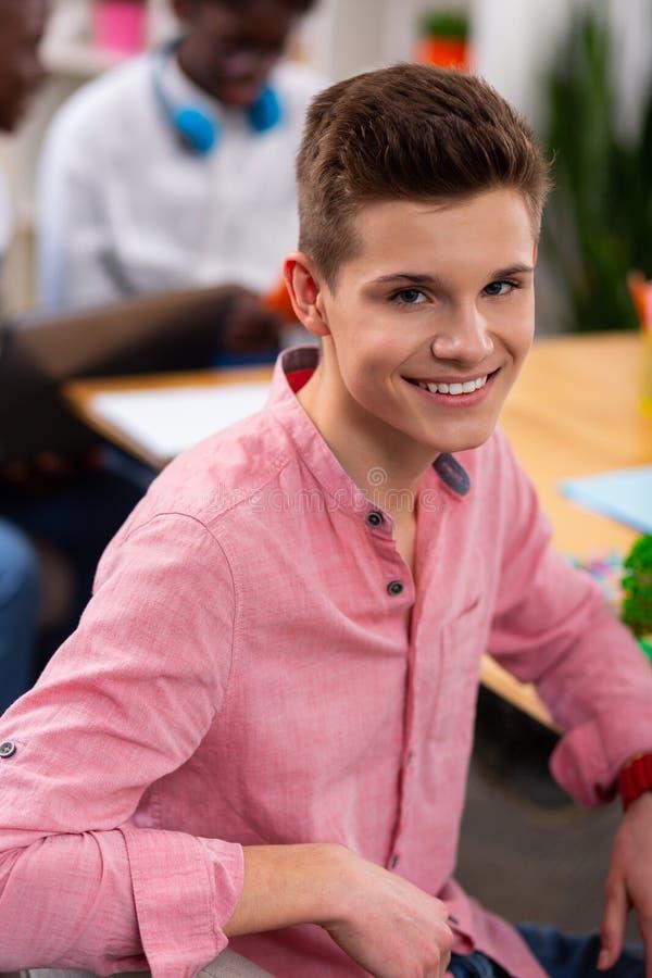 Adolescent bel utilisant la chemise rose souriant largement image stock