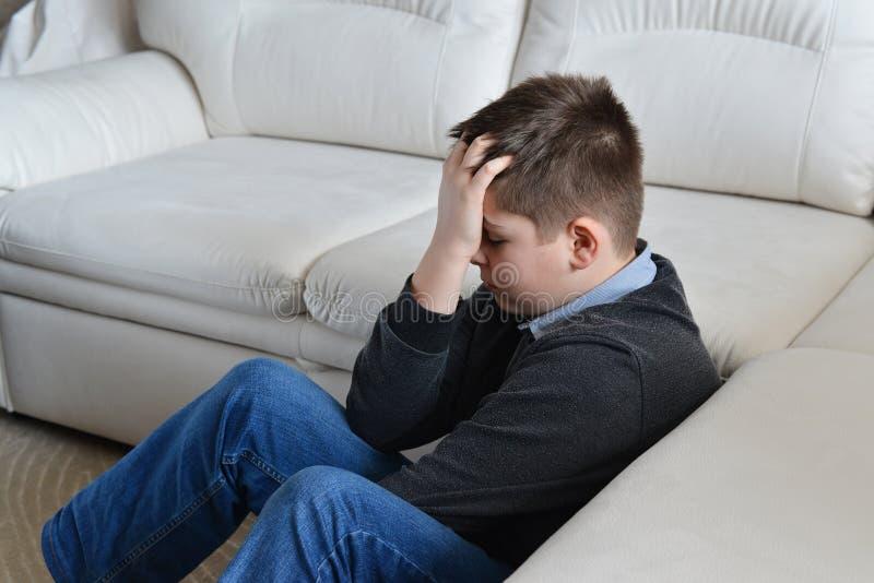 Adolescent bouleversé 13 ans se reposant près du divan et tenant sa tête dans des mains photo stock