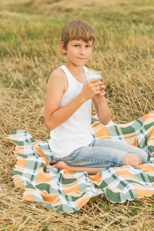Adolescent buvant du lait cru frais du verre photos libres de droits